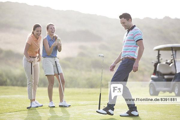 Women watching man balance golf club on foot
