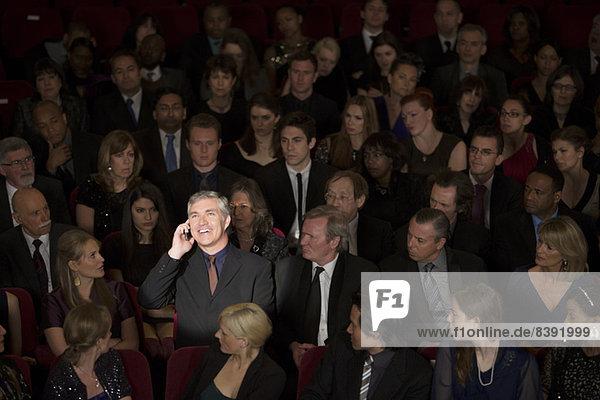 Mann spricht am Handy im Theaterpublikum