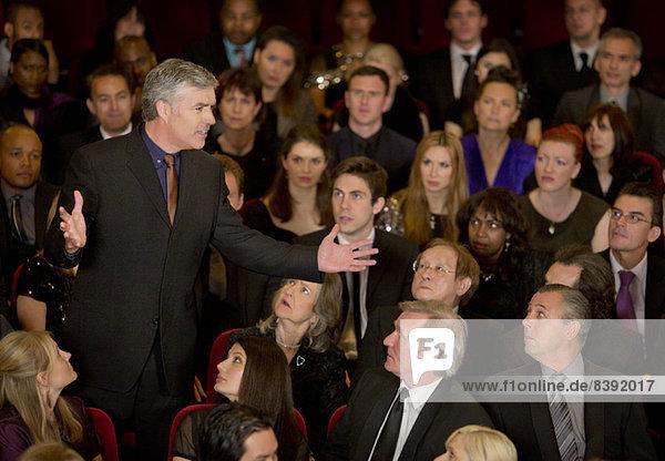 Theaterpublikum beobachtet stehenden Mann mit Gesten