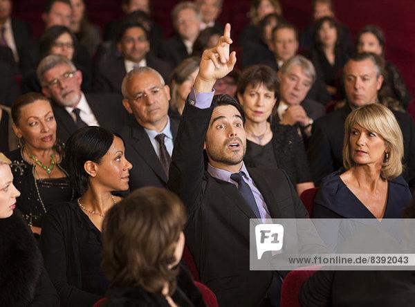 Mann hebt die Hand im Theaterpublikum