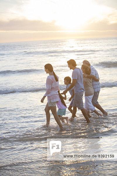 Mehrgenerationen-Familienspaziergang in der Brandung am Strand