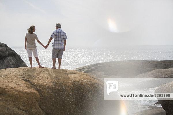 Seniorenpaar hält Hände auf Felsen am Strand