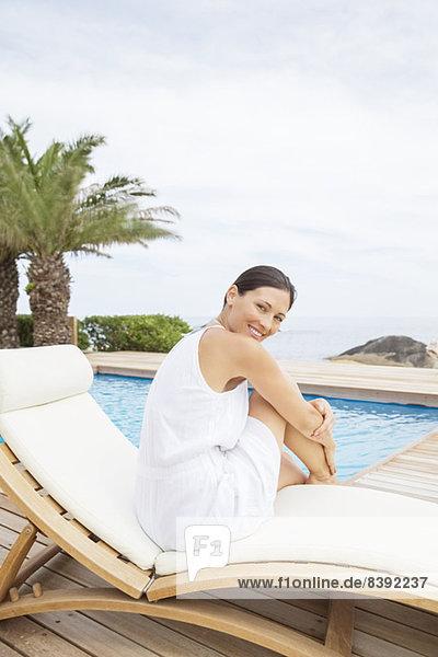 Frau entspannt im Liegestuhl am Pool