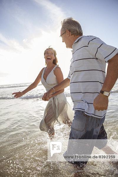 Älteres Paar spielt in Wellen am Strand