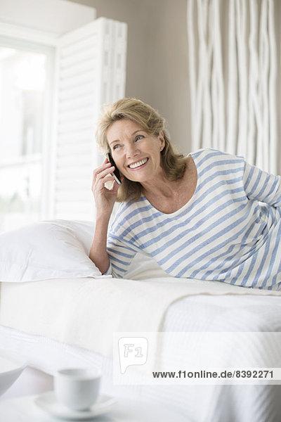 Ältere Frau beim Telefonieren im Bett