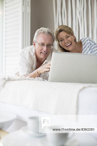Älteres Paar mit Laptop im Bett