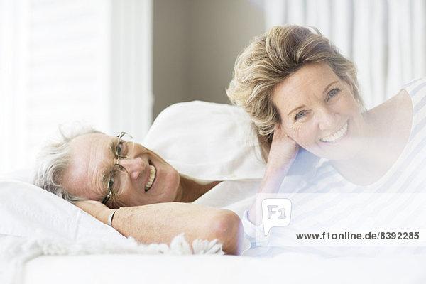 Älteres Paar lächelt auf dem Bett