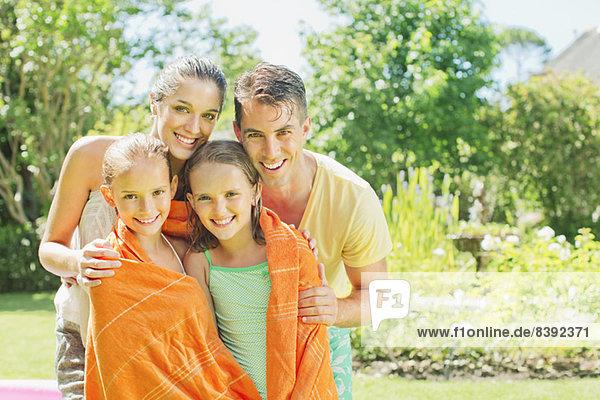 Eltern wickeln Töchter in Handtücher im Garten ein.
