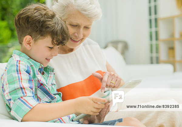 Older woman and grandson using digital tablet