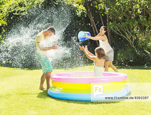 Familie wirft Wasser auf Vater im Hinterhof