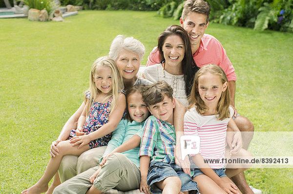 Mehrgenerationen-Familie lächelt zusammen im Hinterhof