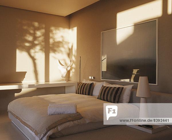 Spiegelung von Bäumen an der Wand im modernen Schlafzimmer