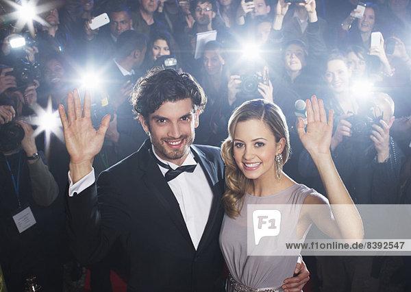 Prominentenpaar winkt auf rotem Teppich mit Paparazzi im Hintergrund