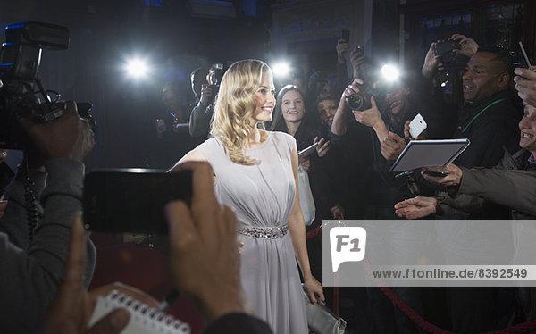 Weibliche Berühmtheit posiert für Paparazzi auf rotem Teppich