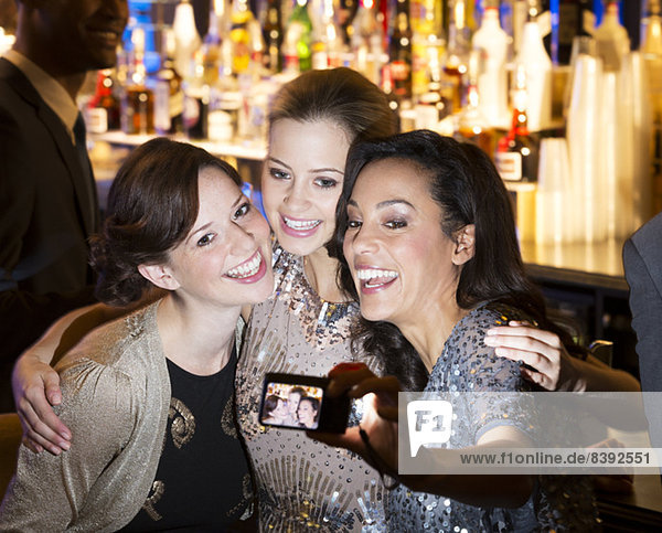 Smiling women hugging and taking self-portrait in nightclub