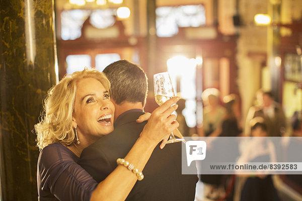 Enthusiastische Frau mit Champagner umarmendem Mann in der Theaterlobby