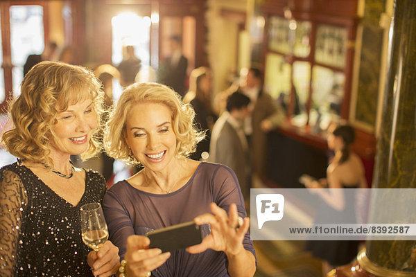 Gut gekleidete Frauen beim Blick auf das Handy in der Theaterlobby