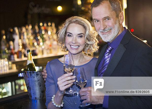 Porträt eines gut gekleideten Paares  das in einer Luxusbar Champagner trinkt.