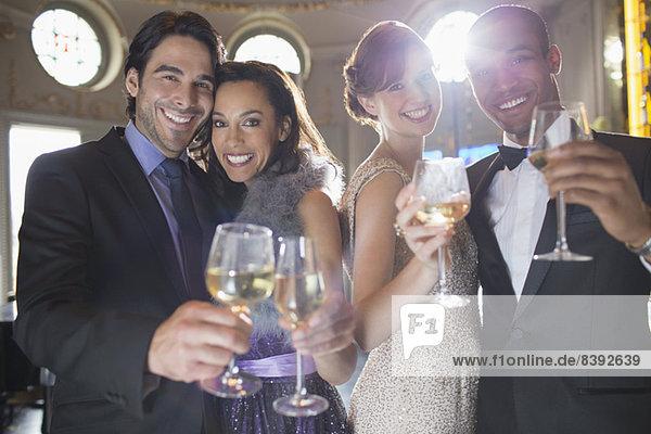 Porträt von gut gekleideten Paaren  die auf Champagner und Weingläser anstoßen.