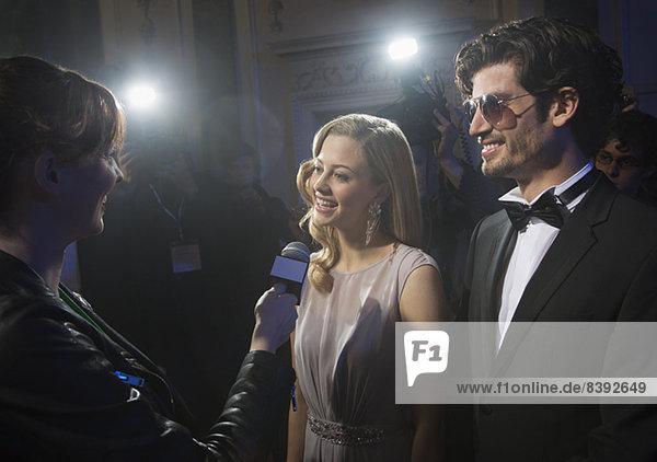 Gut gekleidetes Promi-Paar im Interview auf dem Roten Teppich