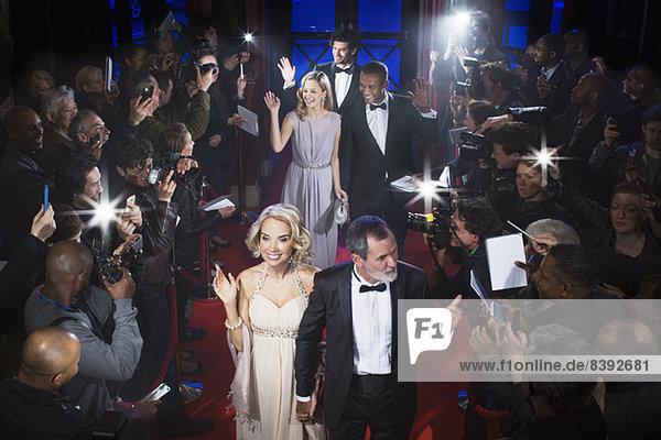 Gut gekleidete Prominente winken den Paparazzi auf dem roten Teppich zu