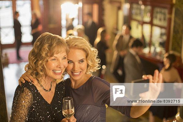 Gut gekleidete Frauen mit Champagner beim Selbstporträt mit Fotohandy in der Theaterlobby
