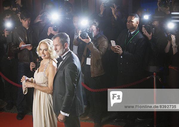 Gut gekleidetes Prominentenpaar posiert für Paparazzi auf rotem Teppich