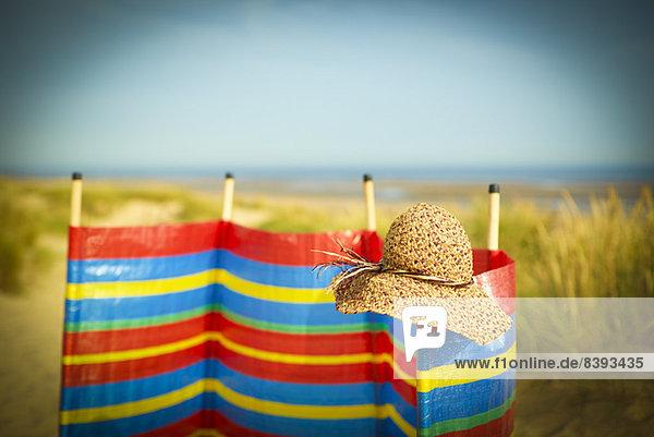 Strohhut auf Windschutz am Strand