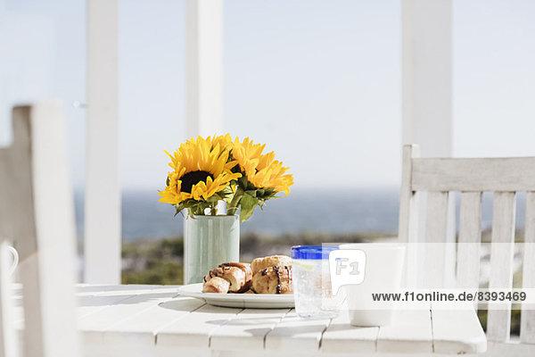 Sonnenblumen und Croissants auf dem Terrassentisch Sonnenblumen und Croissants auf dem Terrassentisch
