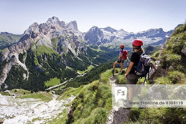 Bergsteiger beim Abstieg  Via ferrata dei Finanzieri im Fassatal  hinten der Gran Vernel und die Marmolada-Südwand  Dolomiten  Trentino  Italien