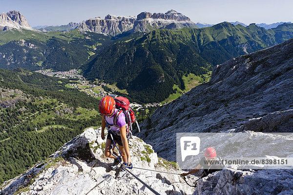 Bergsteiger beim Aufstieg über die Via ferrata dei Finanzieri auf den Colàc im Fassatal  unten das Dorf Alba  hinten der Langkofel  das Pordoijoch und der Sellastock  Dolomiten  Trentino  Italien
