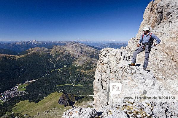 Bergsteiger beim Aufstieg über die Via ferrata Bolver-Lugli auf die Cima Vezzana in der Palagruppe  auch Pale di San Martino  unten das Dorf San Martino di Castrozza  Trentino  Italien
