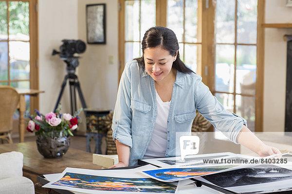 Mixed race photographer examining prints