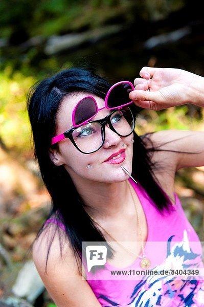 hoch  oben  Portrait  Frau  heben  braunhaarig  Gesichtsausdruck  Gesichtsausdrücke  Ausdruck  Ausdrücke  Mimik  Sonnenbrille  Piercing  20  alt  Jahr