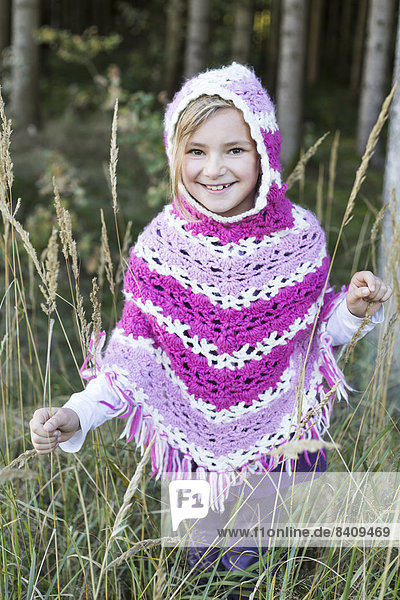 Girl in forest  wearing poncho
