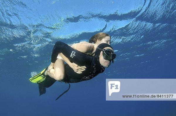 Freitaucher oder Apnoetaucher trägt eine Frau huckepack  Symi  Ägäis  Griechenland