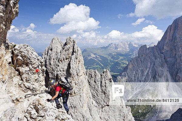 Bergsteiger beim Aufstieg auf den Plattkofel über den Oskar-Schuster-Stieg  Klettersteig  hinten die Geislerspitzen  Gröden  Dolomiten  Südtirol  Italien