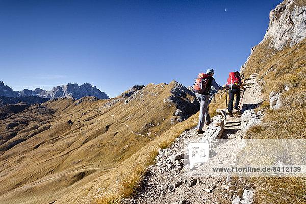 Bergsteiger auf der Peitlerscharte beim Aufstieg auf den Peitlerkofel im Naturpark Puez-Geisler  hinten das Kreuzkofeljoch und die Geislerspitzen  Dolomiten  Südtirol  Italien
