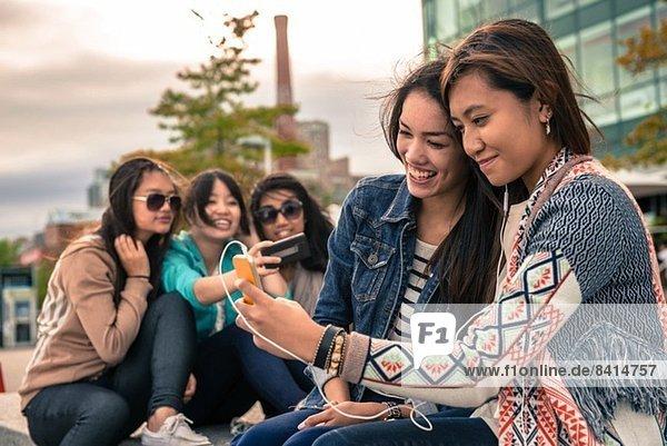 Junge Frauen beim Fotografieren von Selbstporträts mit Smartphones