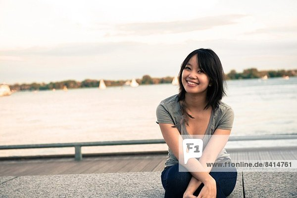 Young woman sitting at waterfront
