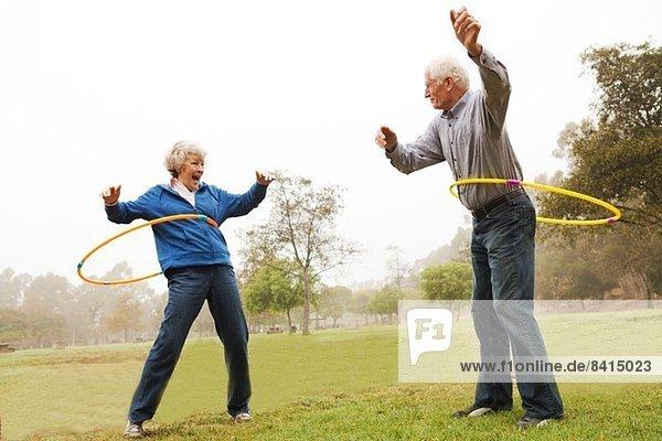 Mann und Frau spielen Hula Hoop im Park