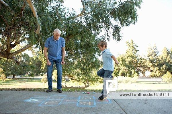 Junge auf Hüpfburg  Großvater schaut zu