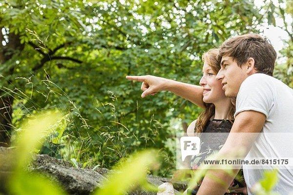 Paar im Park  mit dem Finger zeigen