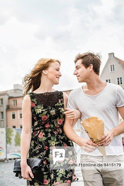 Junges Paar  das durch die Stadt läuft  Arm in Arm Junges Paar, das durch die Stadt läuft, Arm in Arm