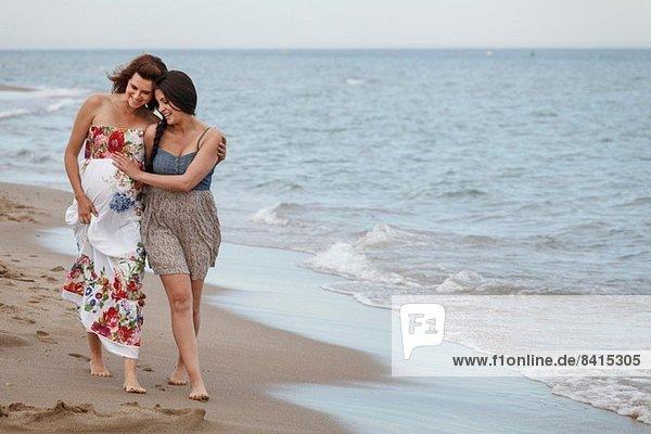 Frauen  die mit dem Arm am Ufer entlanggehen  eine schwanger.