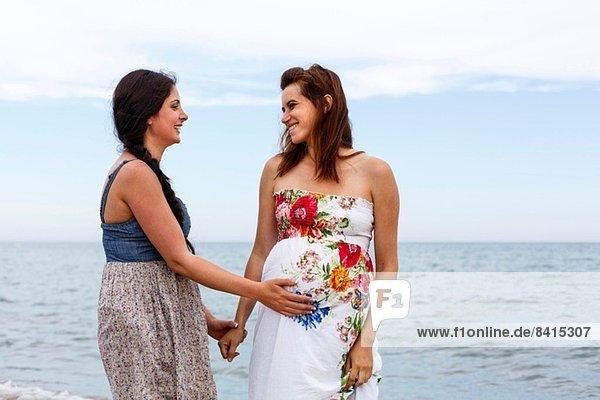 Frau mit Hand auf dem Bauch einer schwangeren Freundin