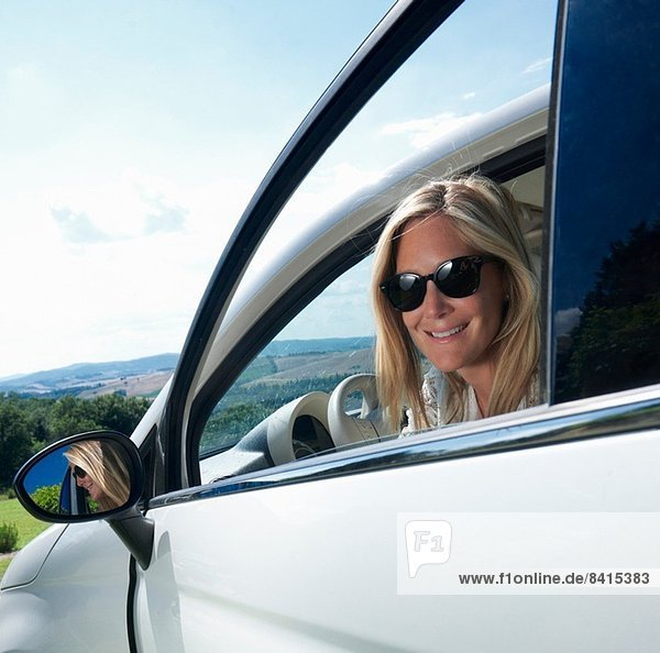 Reife Frau im Auto sitzend