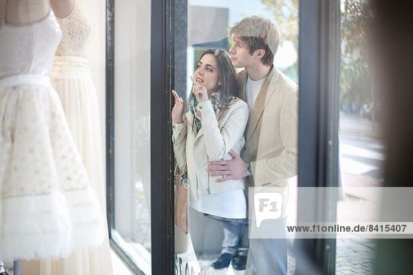 Young couple window shopping  looking through shop front