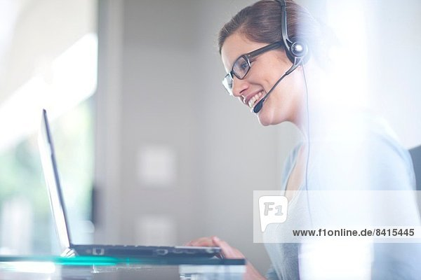 Businesswoman using laptop computer and telephone headset