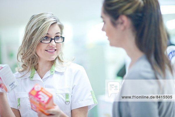 Pharmacist talking to customer  holding boxes of vitamins